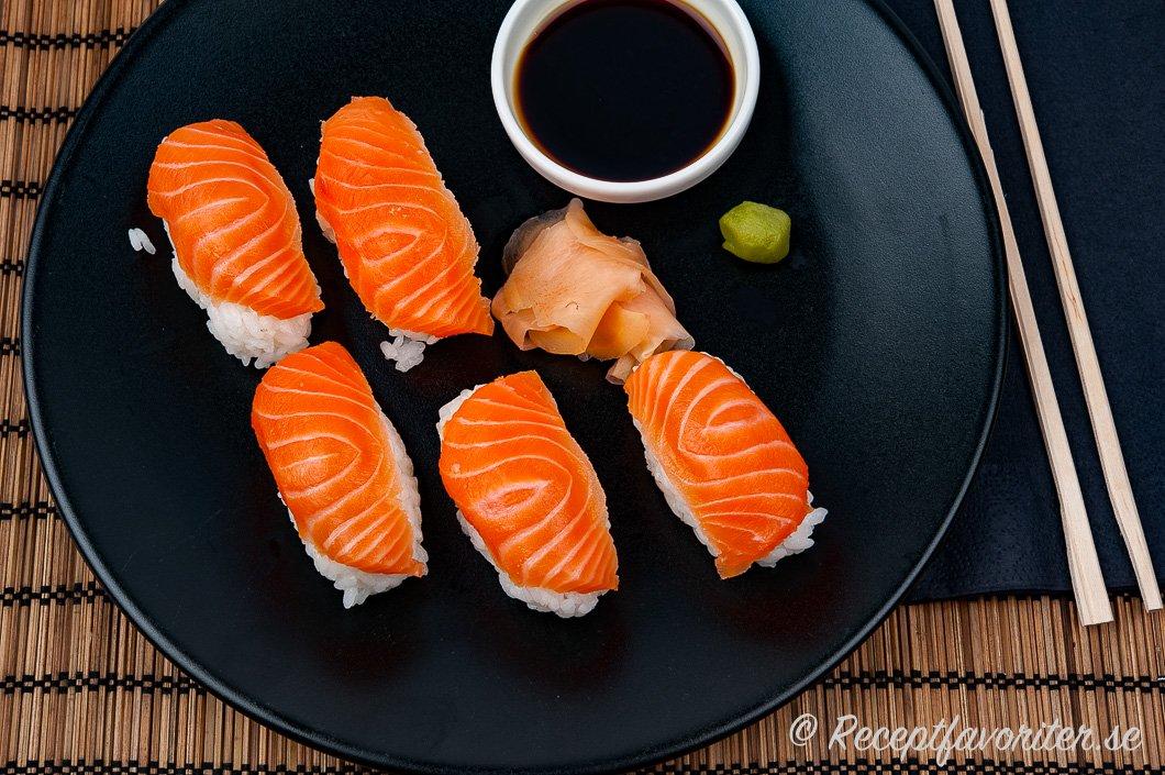 Nigiri sushi med lax och tillbehör på tallrik.