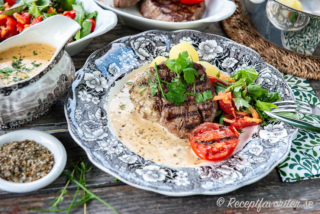 Grillad eller stekt oxfilé på tallrik serverad med varm örtsås och tillbehör.