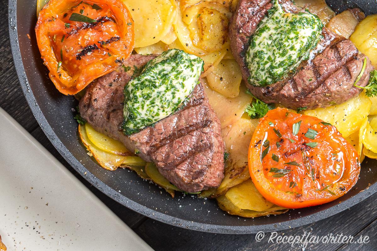 Oxfilén bryns och lagas klart på en bädd av skivad potatis och toppas med vitlökssmör samt serveras med tomat.