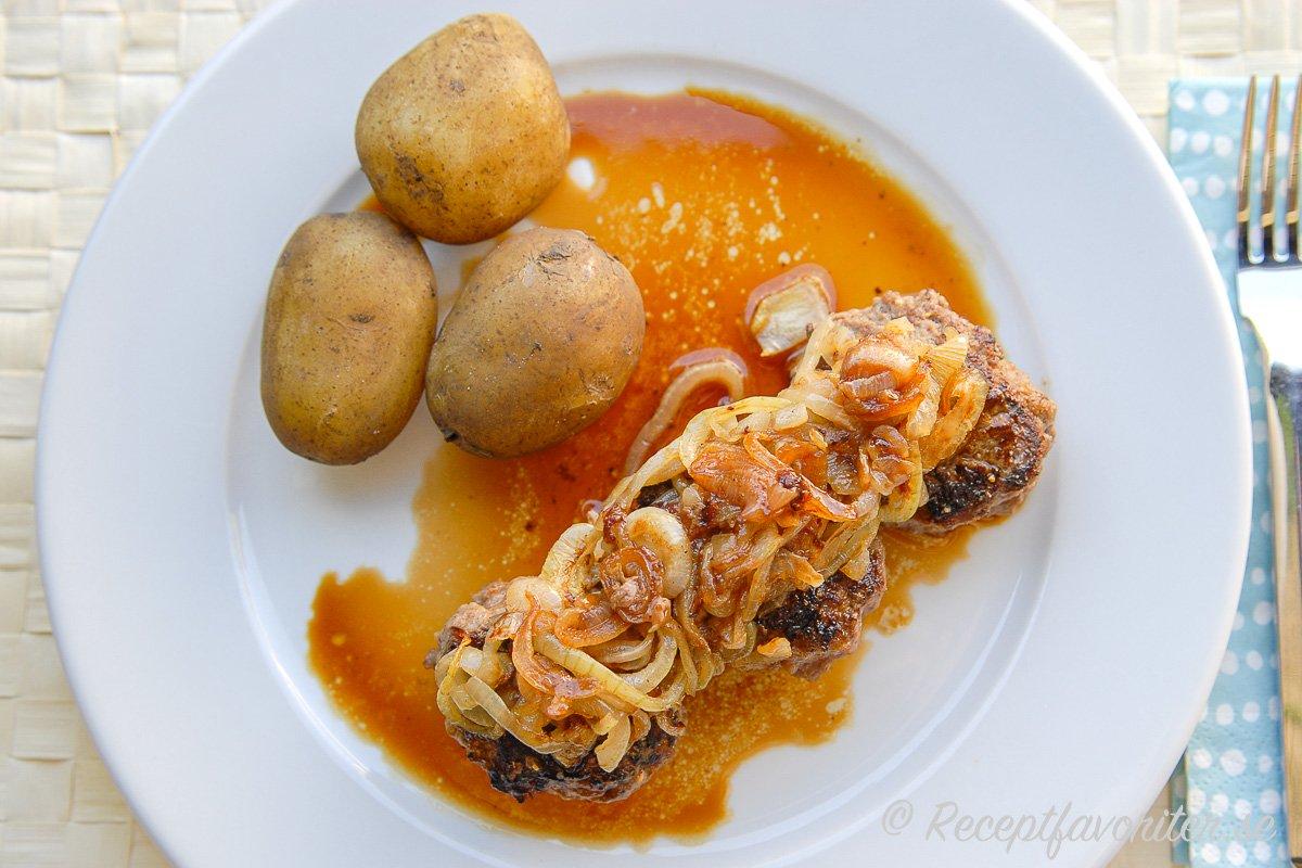 Köttfärsbiffar med stekt lök och skysås samt kokt potatis med skal.