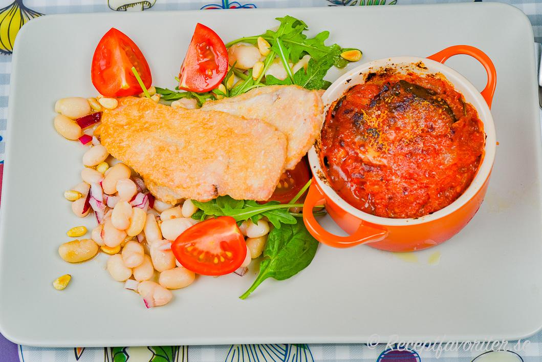 Schnitzel med kyckling och goda tillbehör på tallrik.