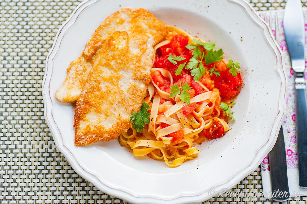 Kycklingfilé panerad med parmesan serverad med pasta i tomatsås.