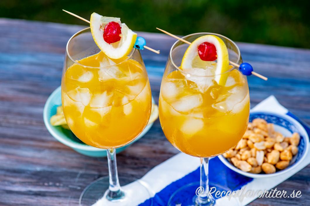 Passionfruit Punch i vinglas med is serverade med chips och jordnötter.