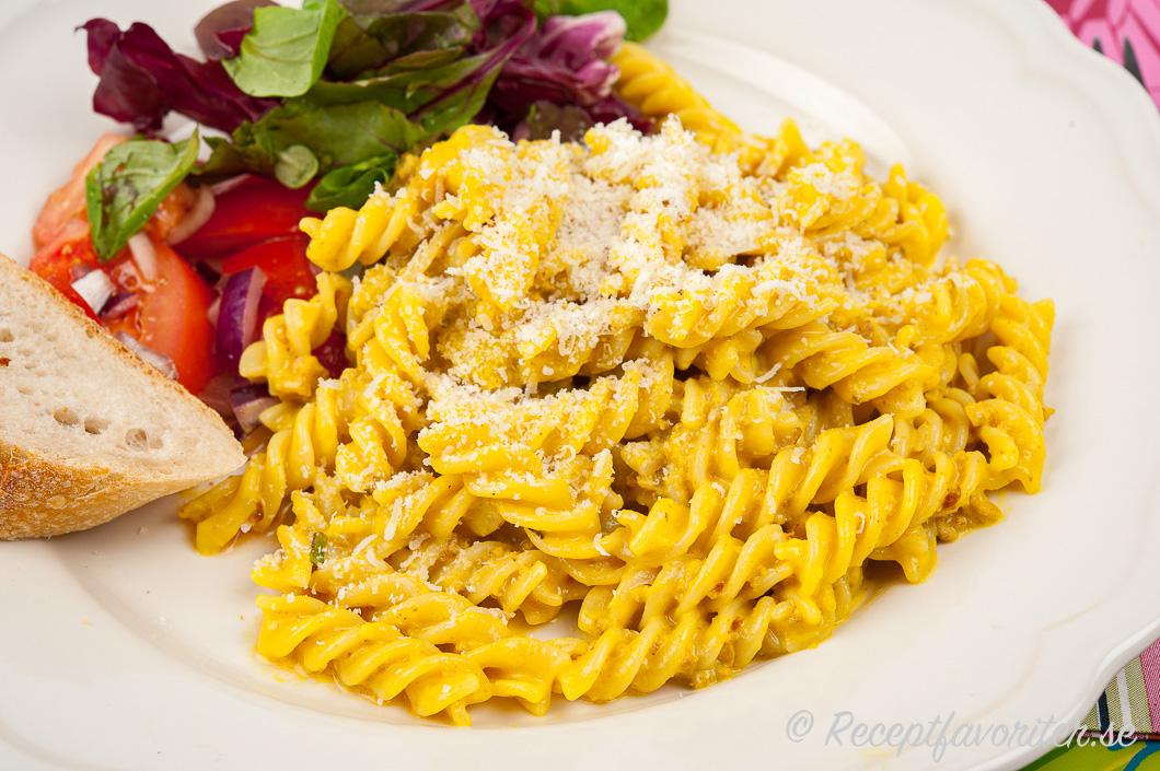 Köttfärssåsen med curry serverad med pasta, grönsallad, tomatsallad och gott bröd på tallrik.