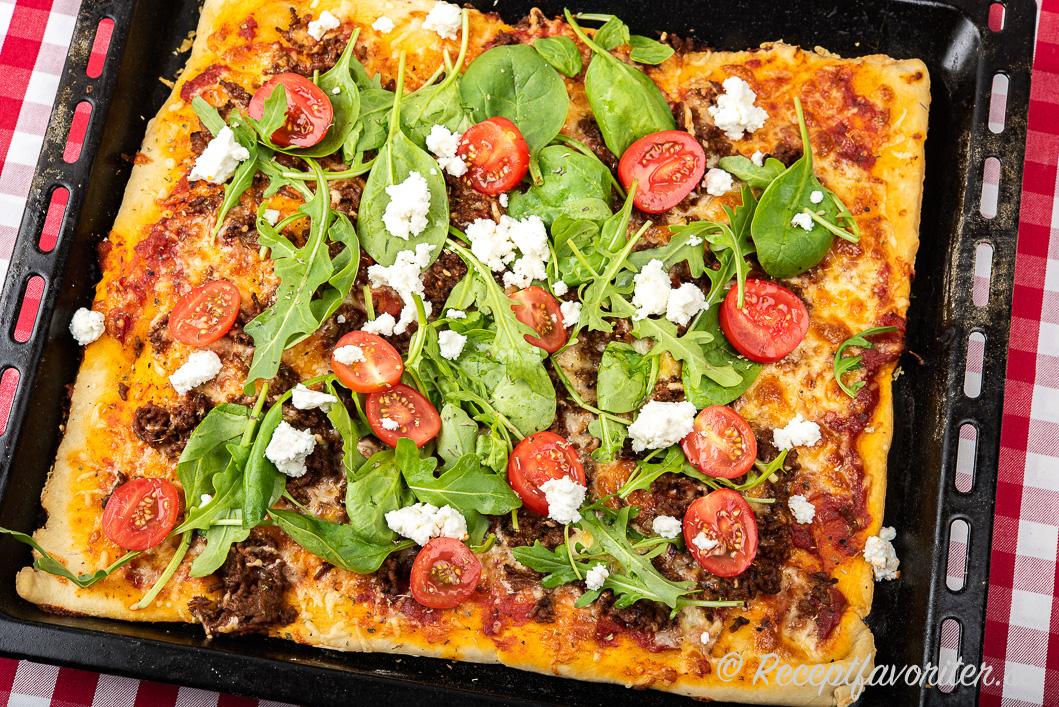 Baka en stor pizza i en långpanna och toppa med de pålägg du gillar