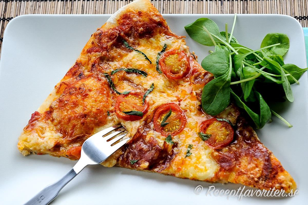 En slize dinkelpizza med lite grönt.