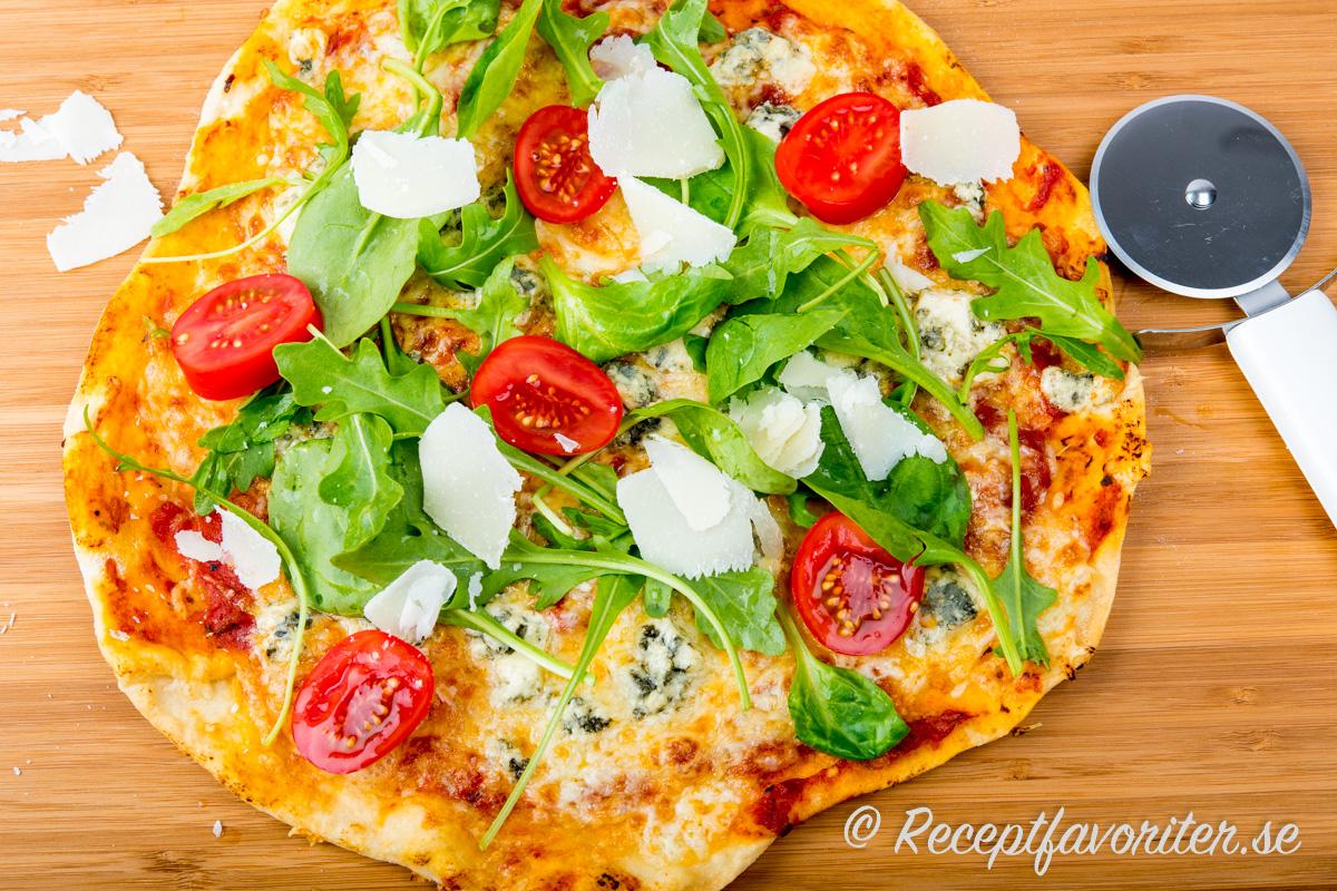 Hembakt gorgonzola- eller ädelostpizza med ruccola, tomat och hyvlad parmesan.