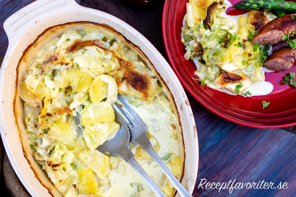 Vitkåls- och potatisgratäng serverad med isterband och grön sparris.