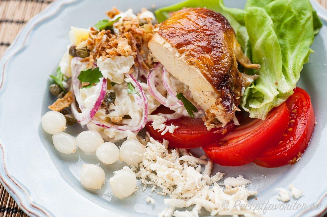 Potatissalladen serverad med grillad kyckling på tallrik med tillbehör