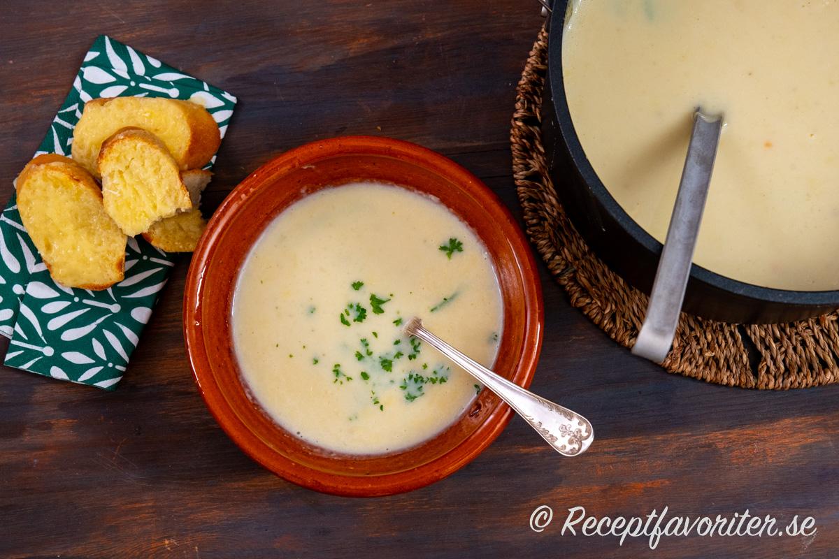 Varm potatissoppa garnerad med hackad kruspersilja och varm baguette med ost till.