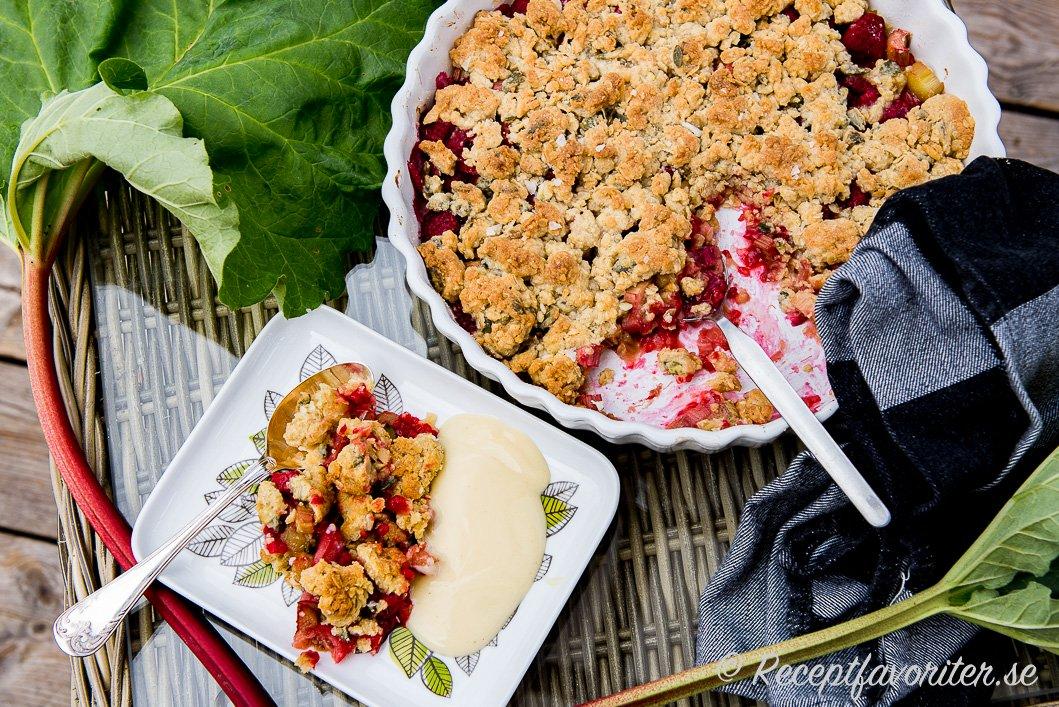 Rabarber och hallon toppad med söt smuldeg med smör, sirap, knapriga pumpafrön och havregryn.