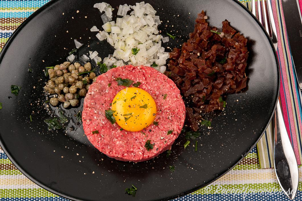 Råbiff av fint nötkött som oxfilé med tillbehör på tallrik.
