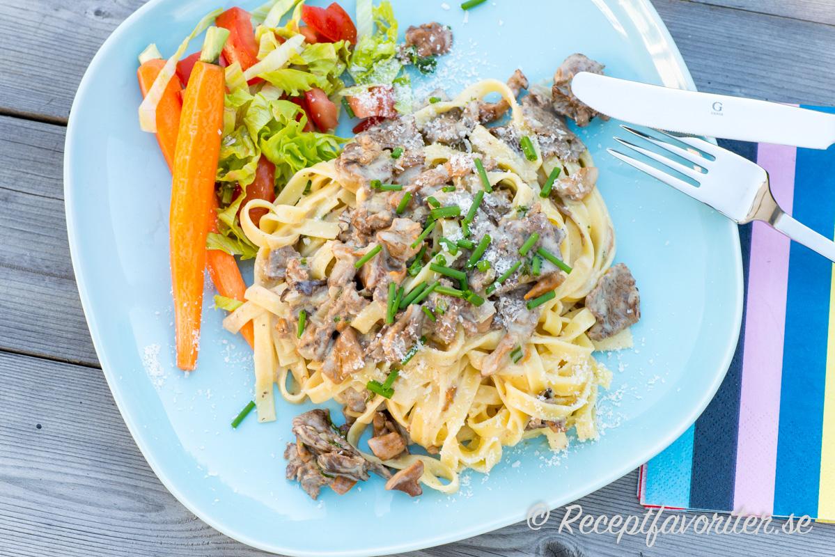 Pasta tagliatelle med renskavssås och hackad gräslök. Serverad med kokt morot, strimlad isbergssallad och tärnad tomat.