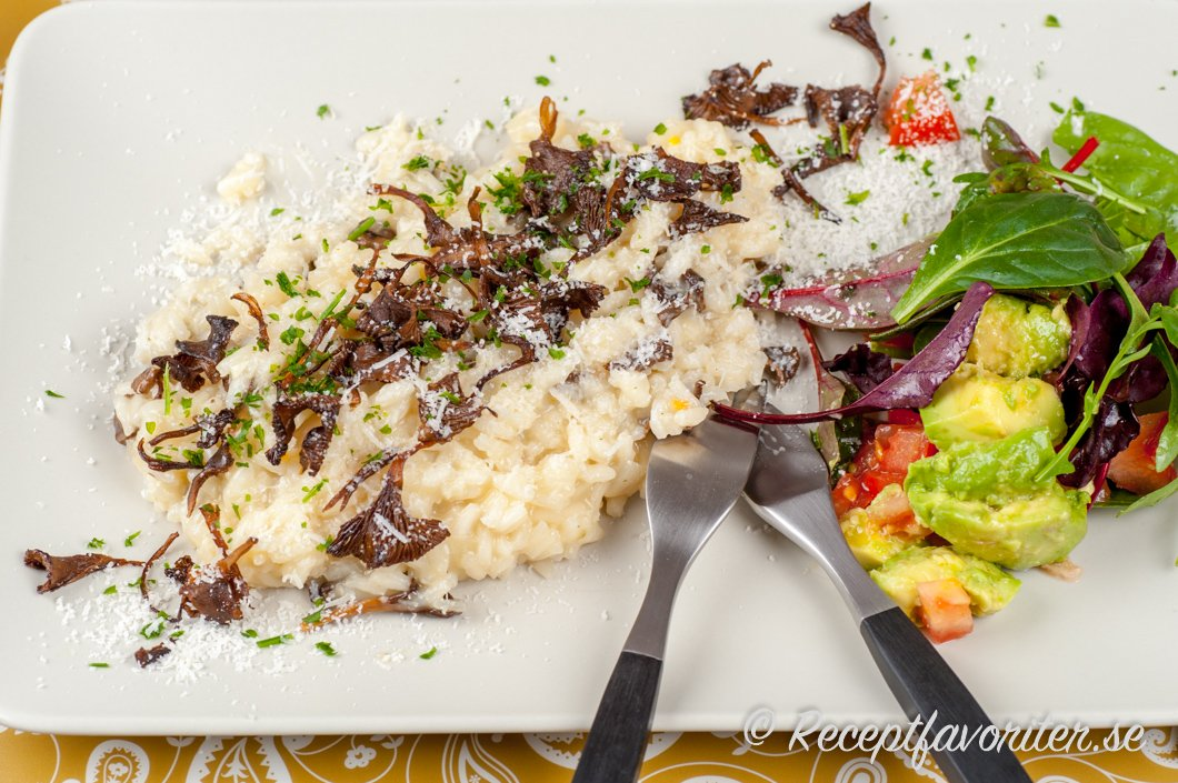 Risotto med torkade trattkantareller serverade med sallad.