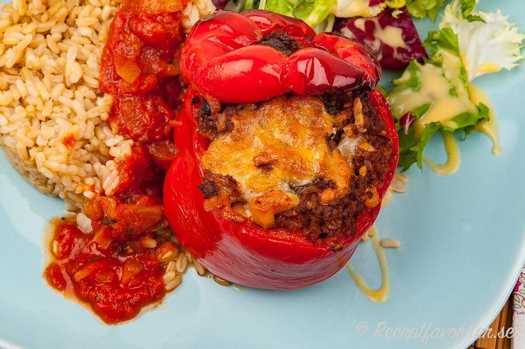 Bakad röd paprika med vegetarisk fyllning serverad med råris, tomatsås och sallad.