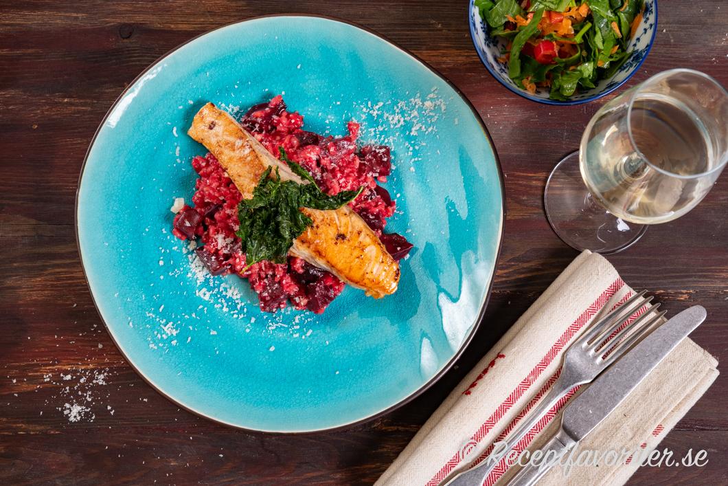 Rödbetsrisotton serverad med stekt lax, grönkålschips, riven parmesan, grönsallad vid sidan och vitt vin som Pinot Grigio.