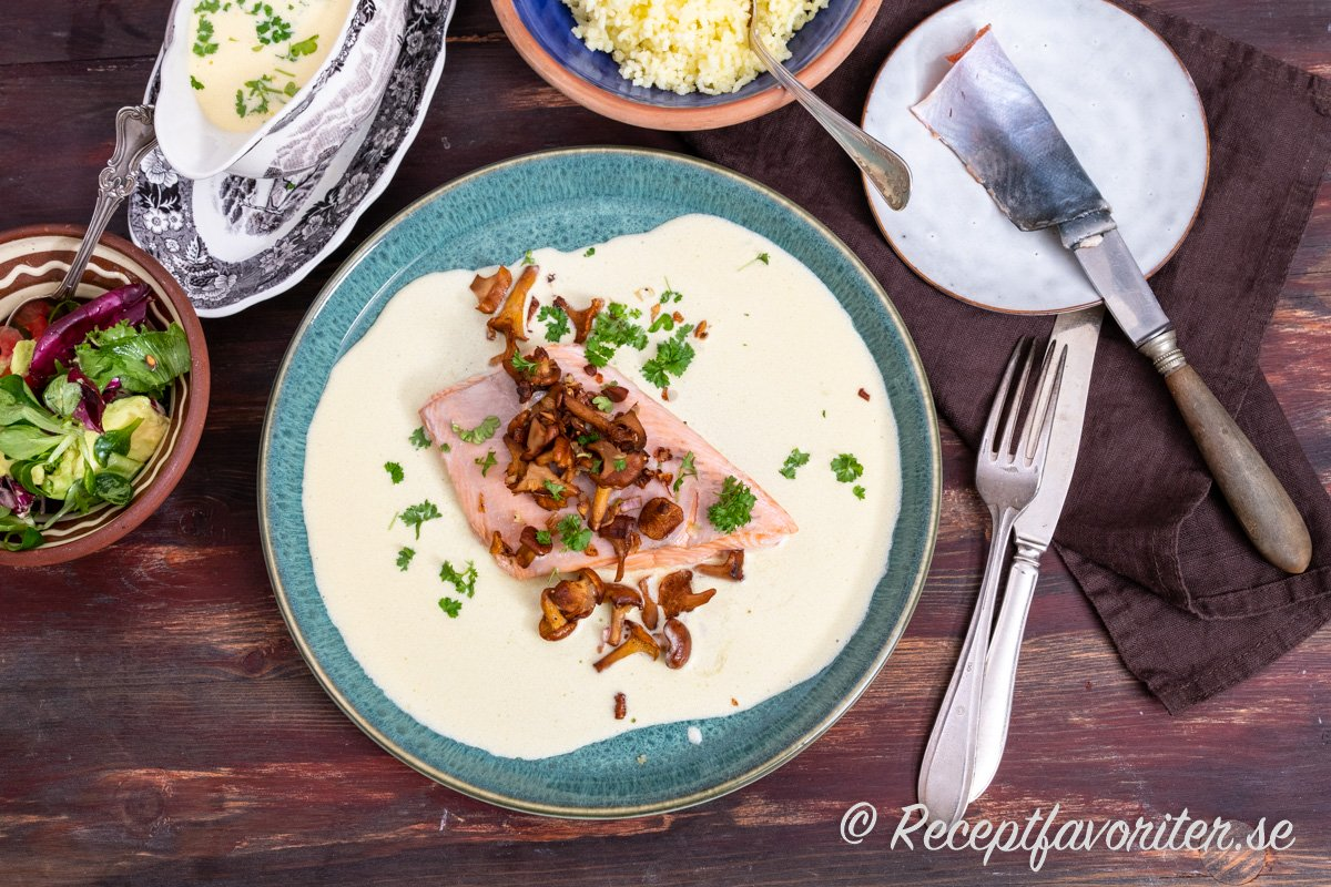 Fjällröding serverad med kantareller och smörsås samt tillbehör på tallrik.