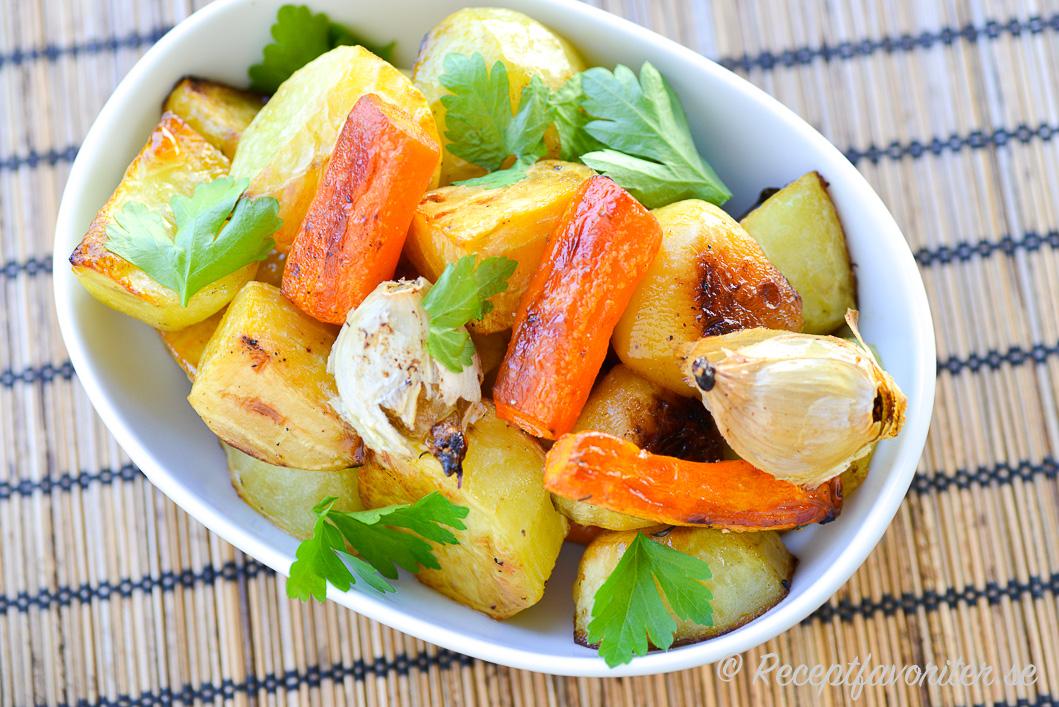 Rostade rotfrukter som potatis, morot, gulbeta med hela klyftor vitlök i skål