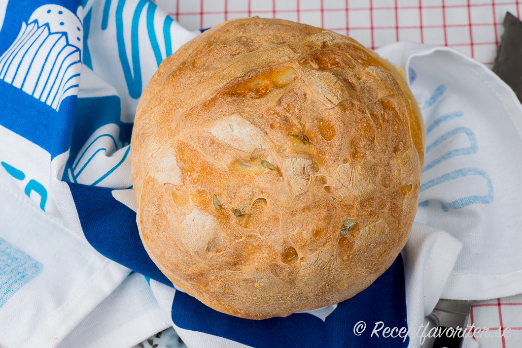 Ett runt matbröd med örter som basilika och rosmarin