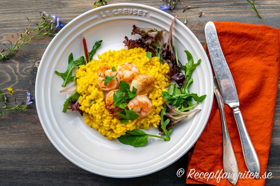 Krämig risotto med smak av saffran, vitt vin, buljong, parmesan och lite vitlök på tallrik med tillbehör.