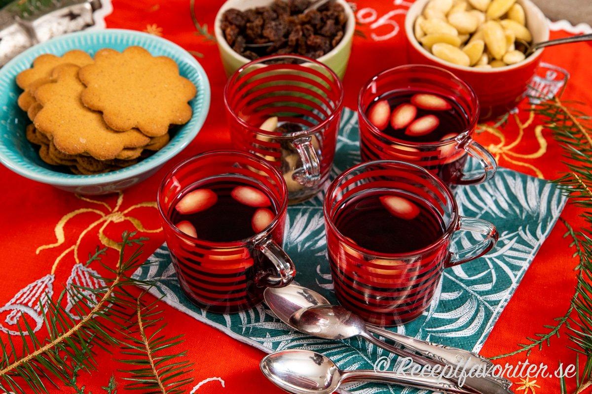 Saftglöggen serverad på klassiskt vis med pepparkakor, mandlar och russin.