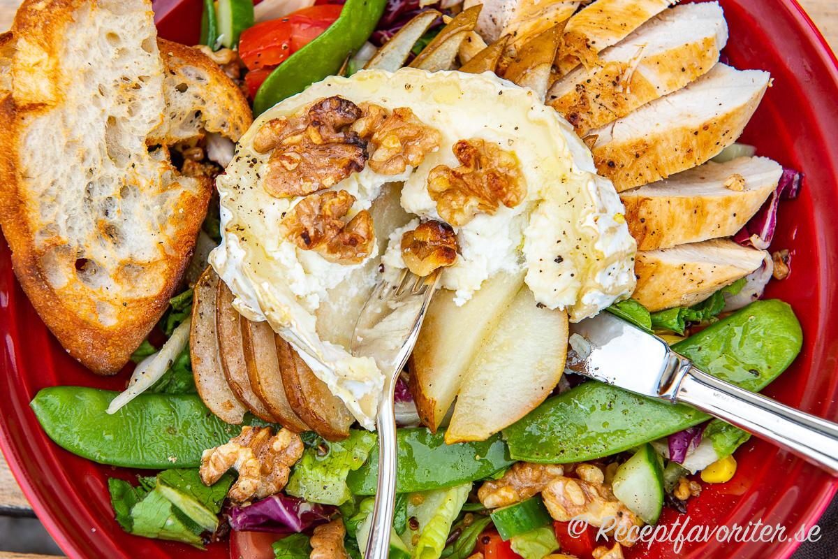 Getost eller chèvre i rulle bakad med honung, valnötter och päron blir mycket gott ihop med kycklingfilé samt sallad på tallrik.