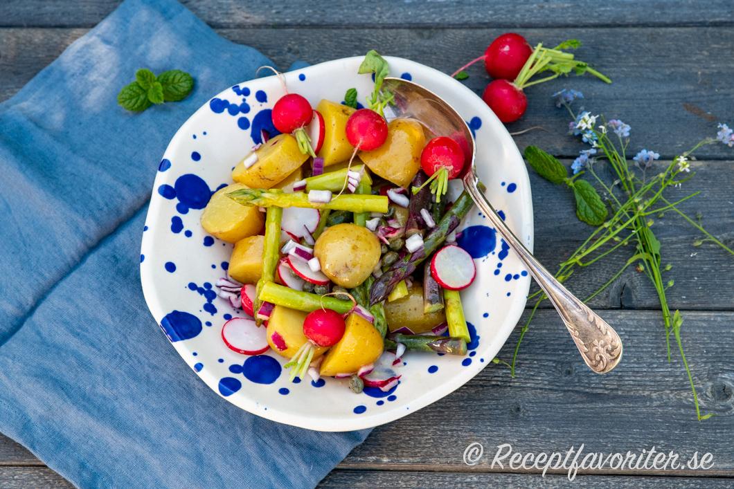 En variant på potatissalladen med kokt grön sparris och rädisor på fat.