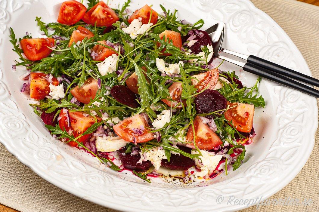 Ett fat med sallad blandad av rödbetor, mozzarella, tomater och ruccola.