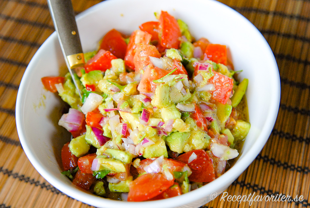 Salsa eller sallad med tomat, avokado och rödlök i skål.