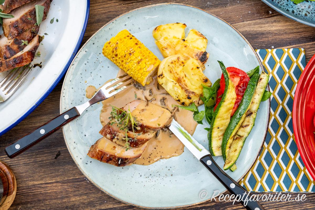 Såsen med torkade trattkantareller serverad på tallrik med grillad vildsvinsytterfilé, smashad färskpotatis, majs, zucchini och sallad av tomat och babyspenat.