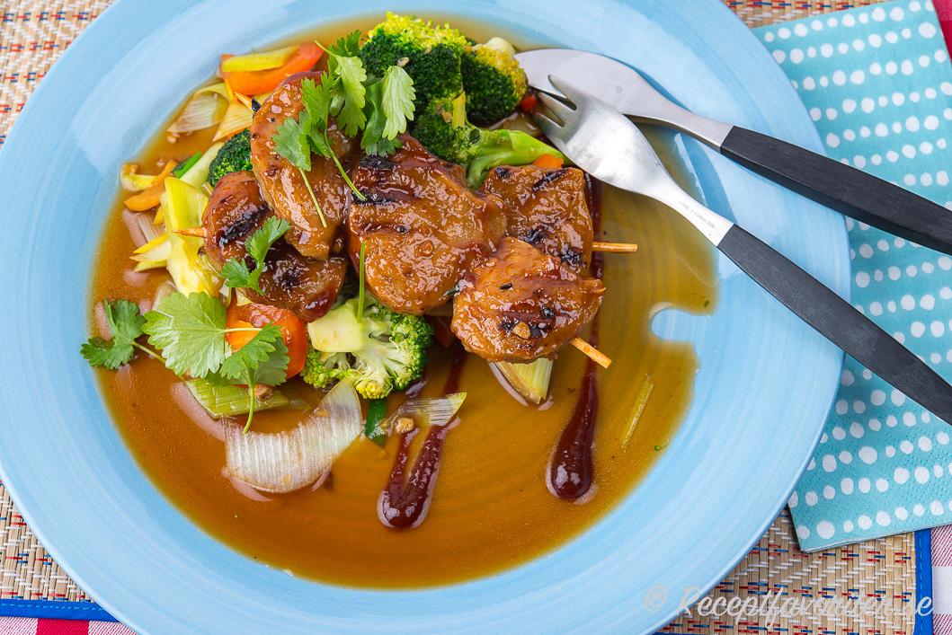 Veganska BBQ-spett med marinerad seitan och wokade grönsaker på tallrik.