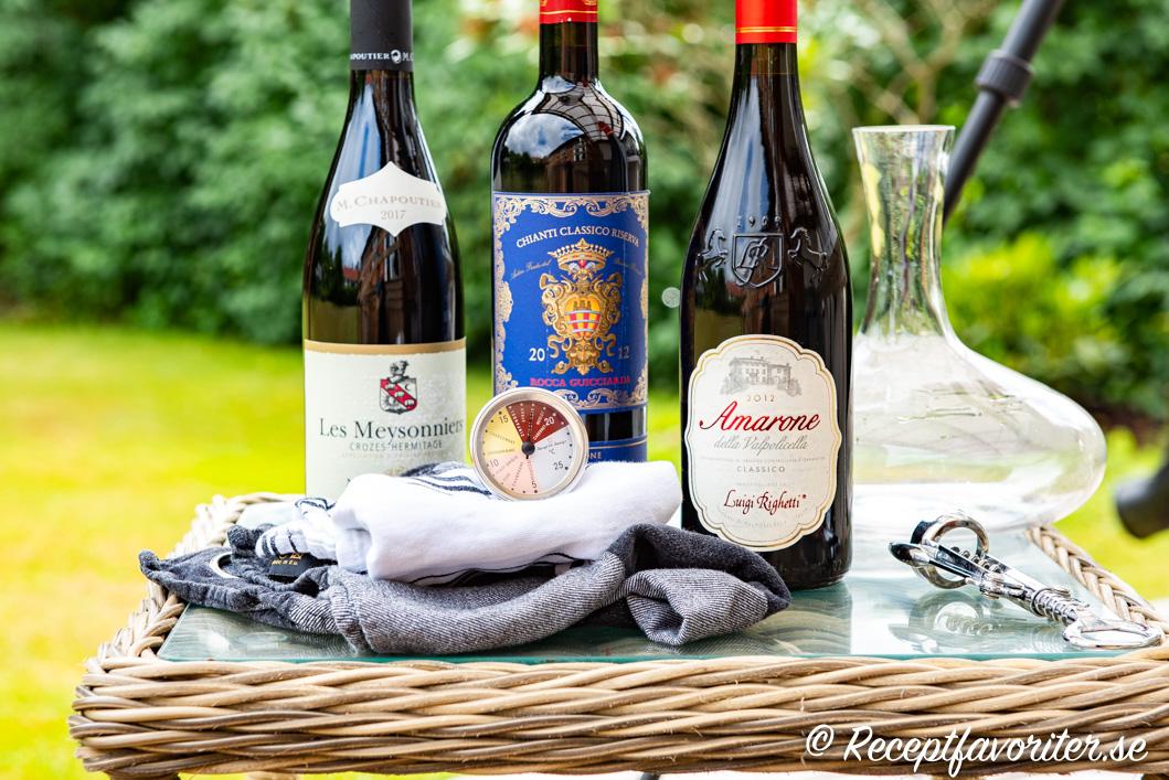 Tre flaskor vin och en vintermometer, karaff för dekantering samt en vinöppnare.