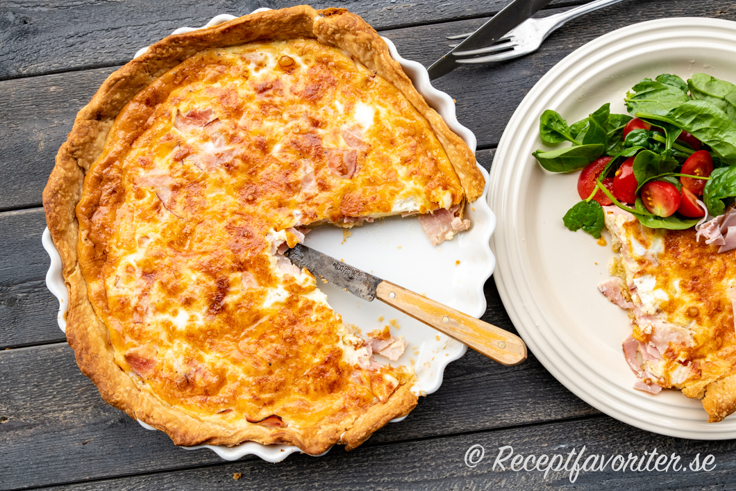 Skinkpaj serverad i bit på tallrik med sallad av babyspenat och små tomater.