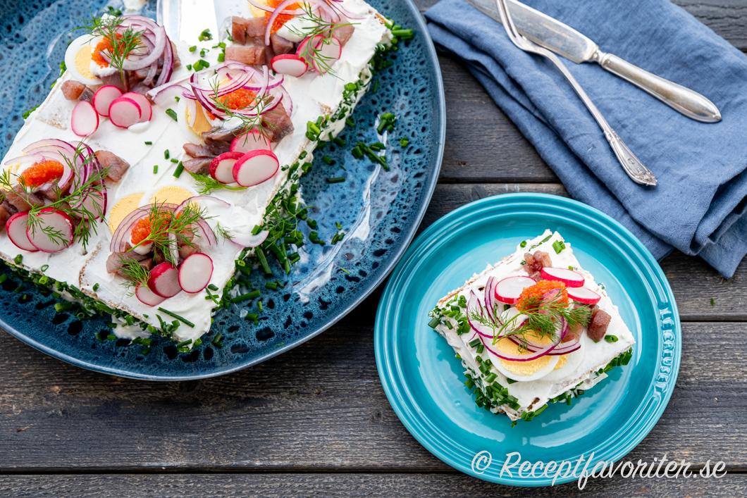 En bit smörgåstårta med matjessill, Västerbottenost och kavring på tallrik