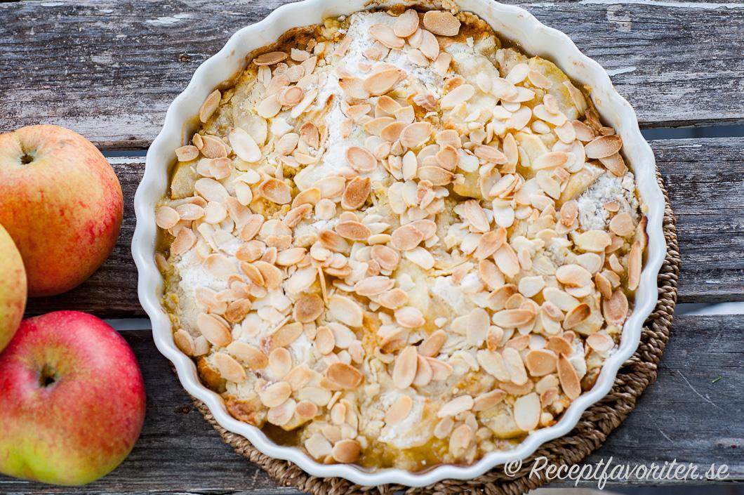 Snabblagad äppelpaj med äpplen toppade med vetemjöl, hyvlat smör och mandel.