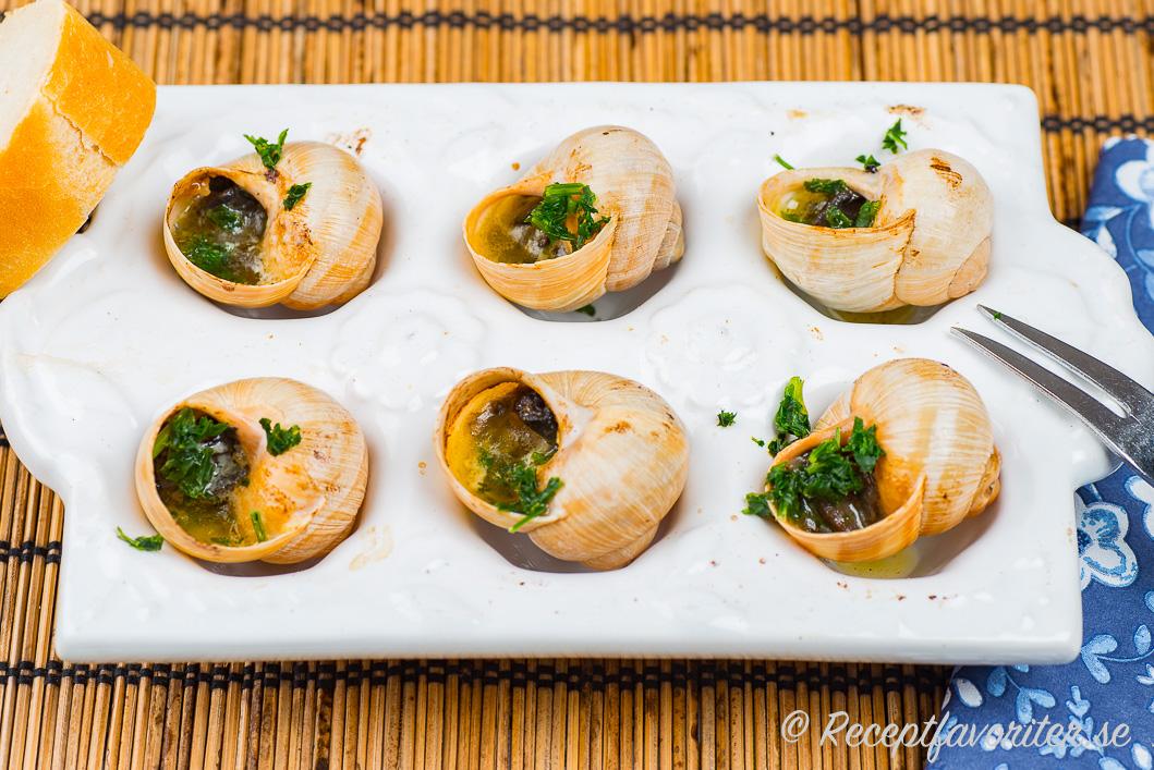 Franska vitlökssniglar serverade med gaffel och baguette