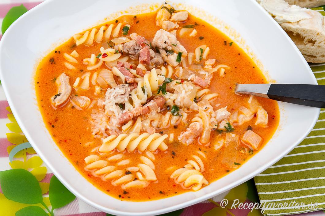 Soppa med pastaskruvar och bacon i tallrik