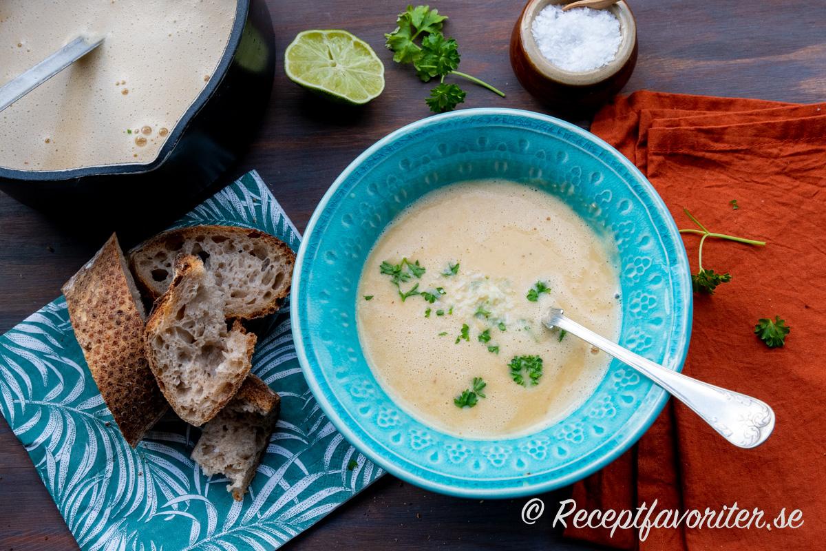 En mixad slät soppa med grund av röda linser, kokosmjölk, röd currypasta, lime och lök samt vitlök.