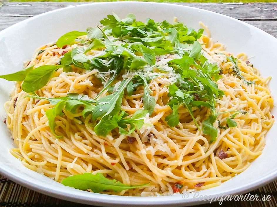 Spagetti på tallrik smaksatt med ruccola, soltorkade tomater och färsk basilika samt riven ost.