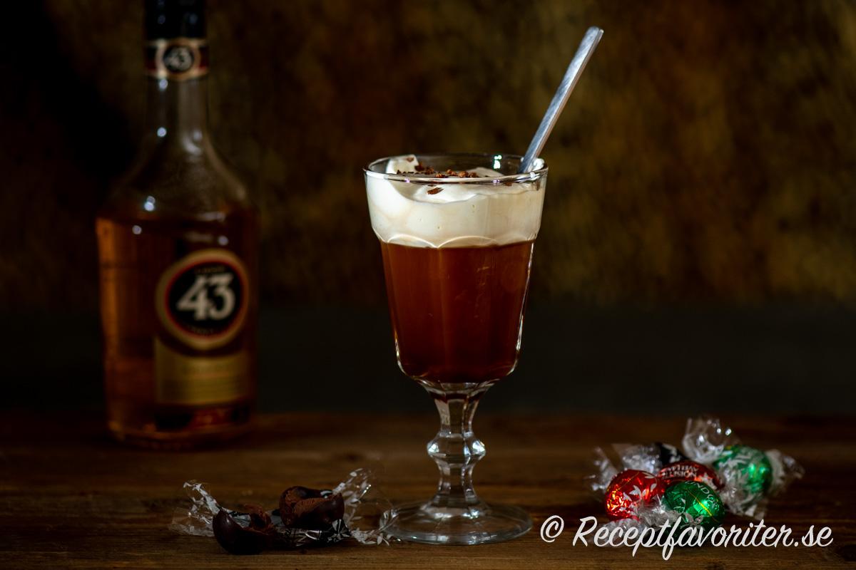 En varm kaffedrink med spansk likör Liqor 43 toppad med kaffe och vispad grädde. Chokladtryfflar vid sidan.