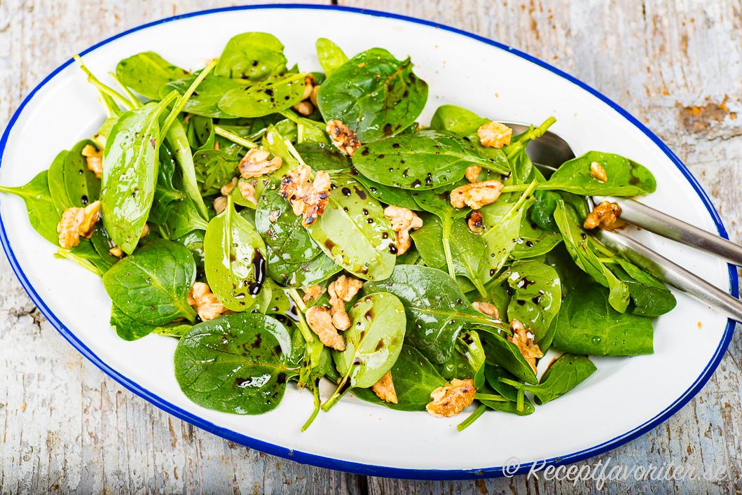 Babyspenatsallad med rostade valnötter, olivolja och balsamvinäger på fat