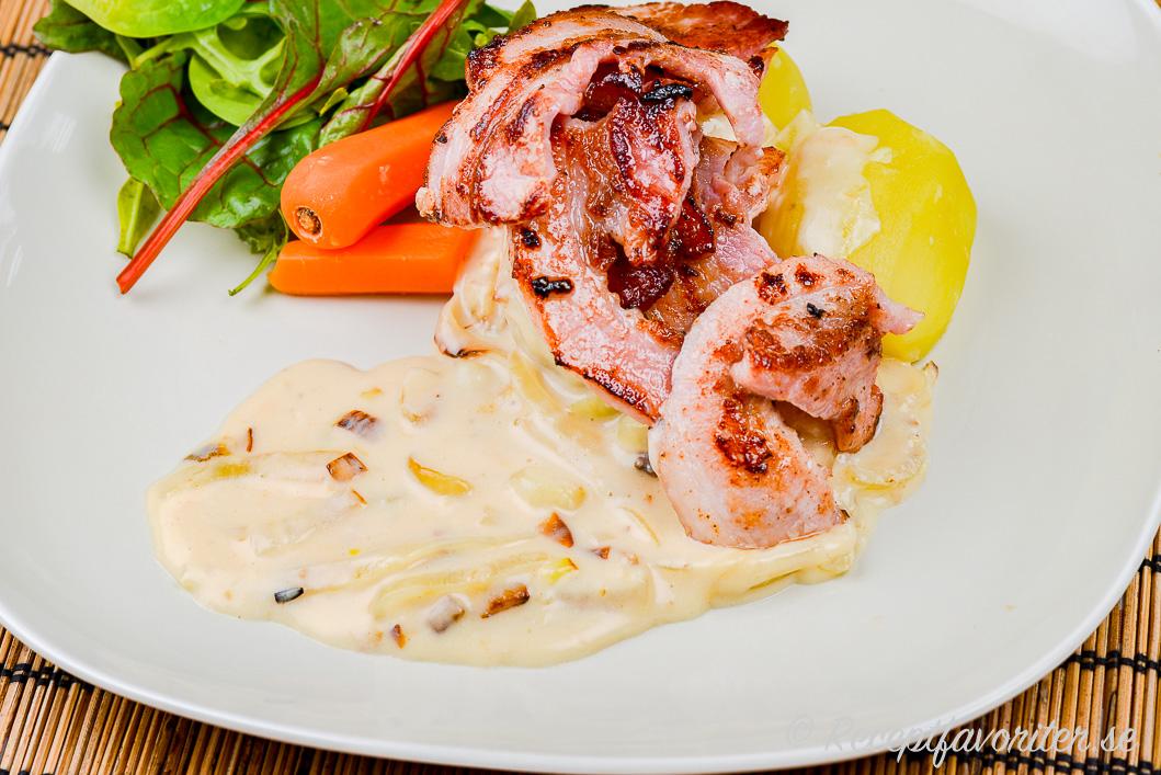 Stekt rimmat fläsk med löksås, grönsallad, kokt morot och potatis på tallrik.
