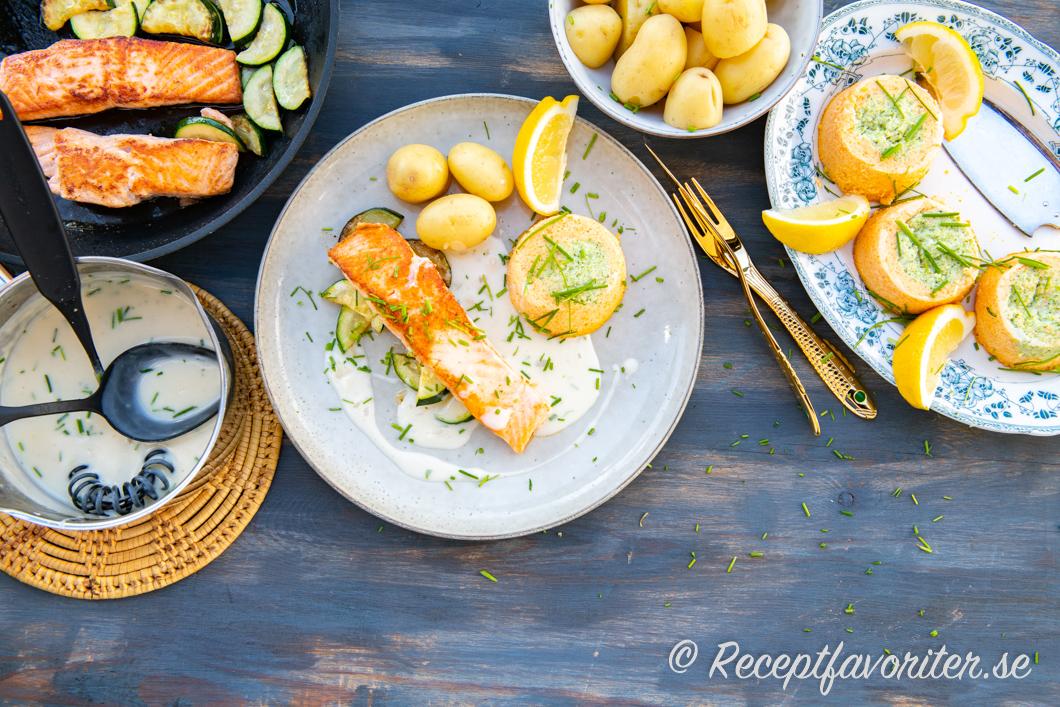 Stekt lax med zucchini, vitvinssås, grönsakstimbaler, kokt potatis och citron.