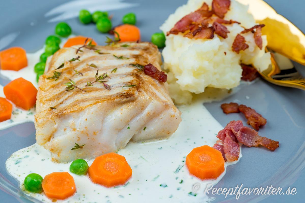 En stekt fin bit torskrygg av norsk Skreietorsk serverad med sås, knaprig bacon, mos, ärtor och morötter.