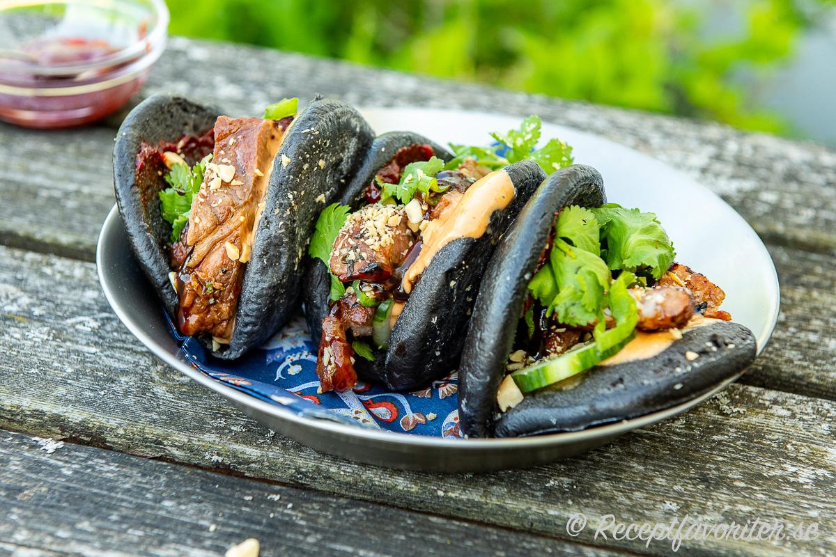 Svarta bao bröd med grillad fläskkarré, sås, grönt och jordnötter.