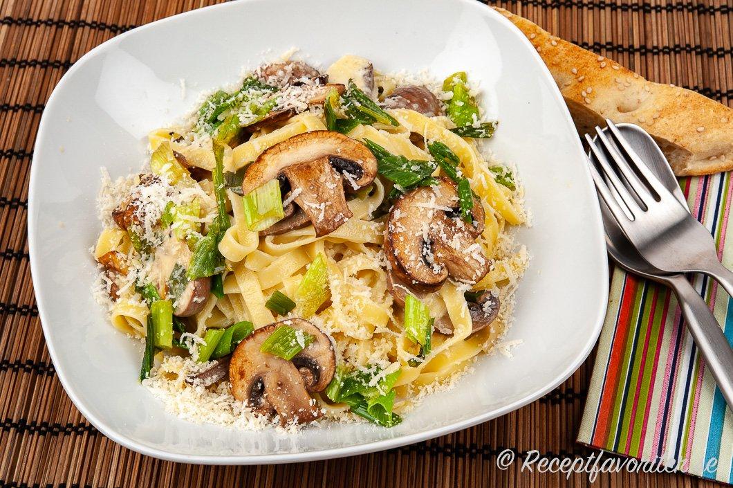 Tagliatelle med champinjoner, grädde, smör, parmesan, vitlök och salladslök i tallrik.