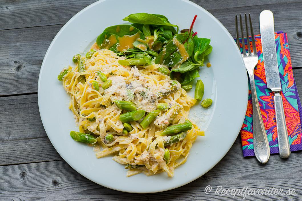 Tagliatelle pasta med sås med krabba, grädde, sparris och bönor.