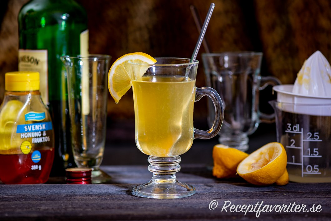 Hot Toddy serverad i glas omgiven av ingredienser