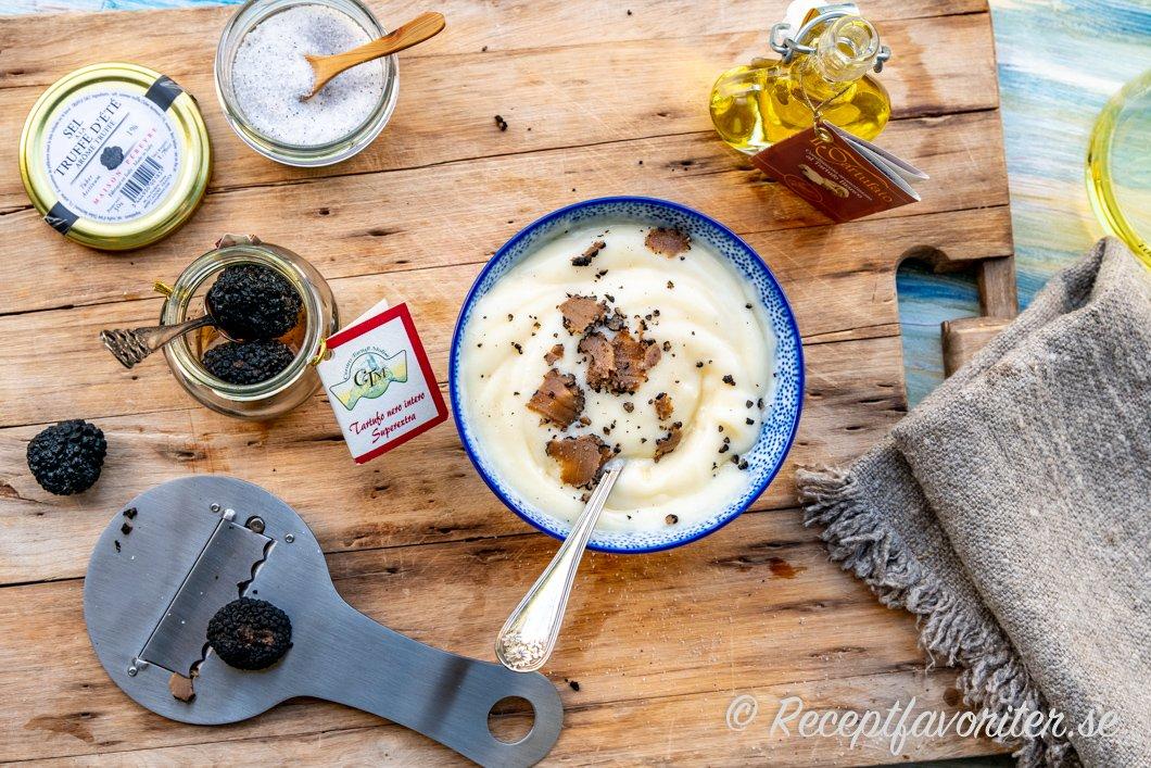 Tryffelmajonnäs i skål omgiven av tre sorters tryffelsmaksättning - tryffelsalt, tryffelolja och hel tryffel.