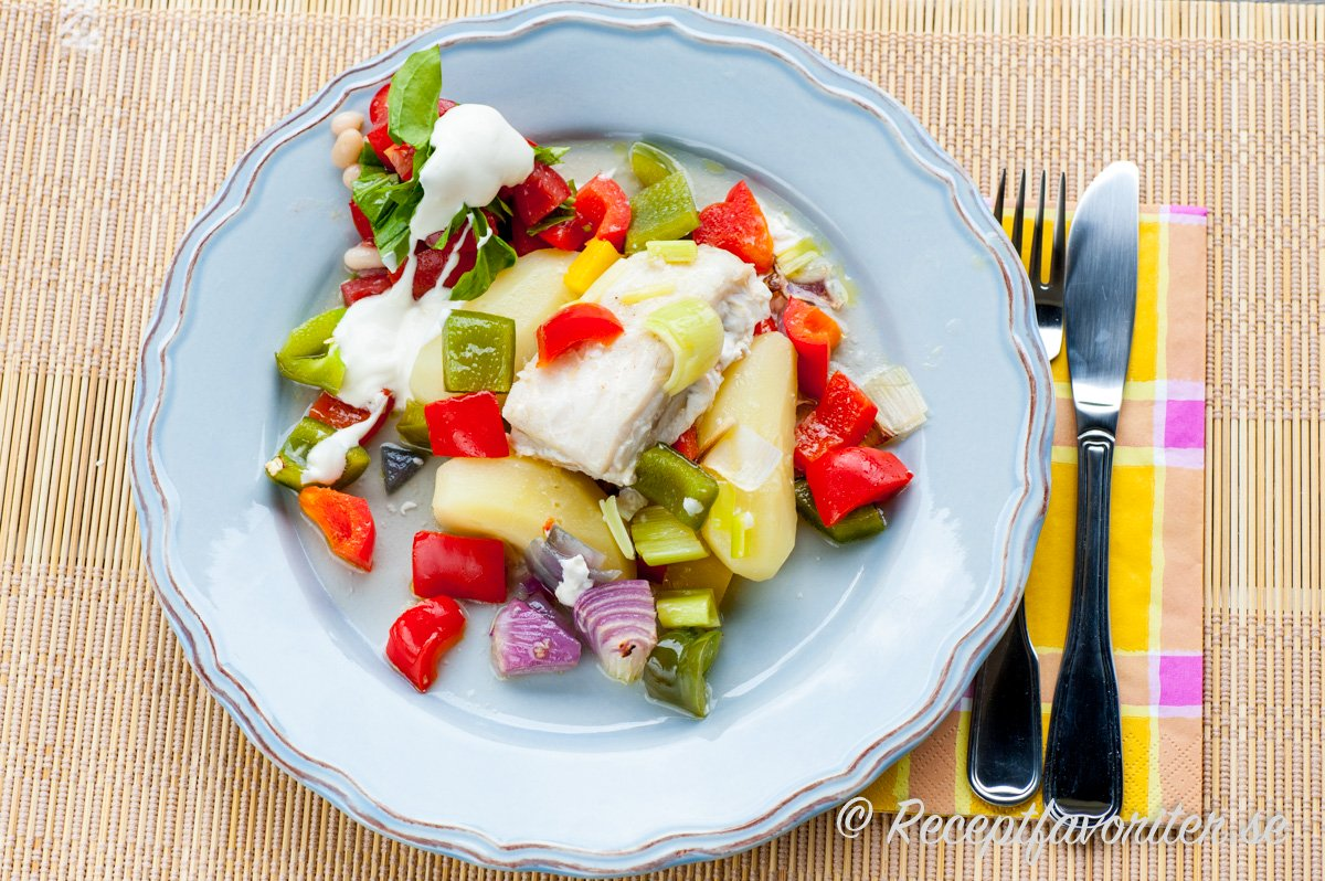 En tallrik torskfilé tillagad i ugnen med grönsaker serverad med potatis och lite kall sås.